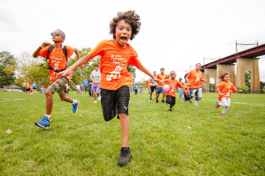 Kids in orange KEEN branded shirts running towards the camera.