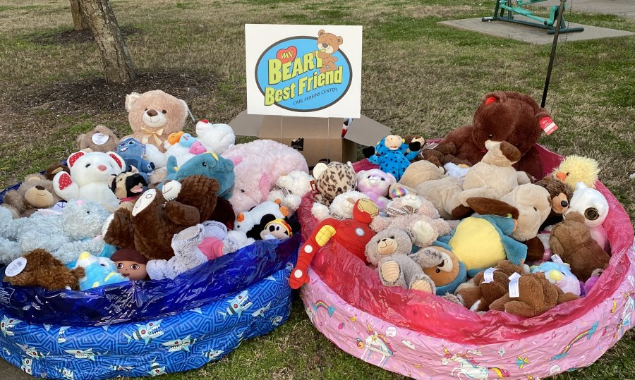 Two small inflatable pools full of stuffed animals with a sign that says Beary Best Friends