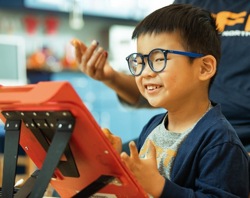 Young boy with blue rimmed glasses smiling  while he finger paints.